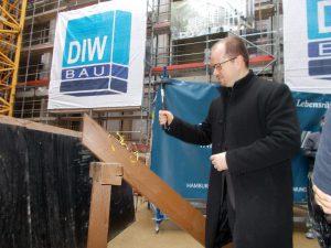 Niels Nirenberg, PPa und Projektleiter des planenden Architekturbüros MPP Meding Plan & Projekt GmbH, schlägt den symbolischen letzten Nagel ein